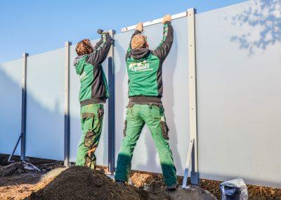 Ein Sichtschutz wird von zwei Mitarbeitern montiert